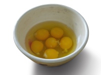 Six cracked eggs in bowl with black shadow